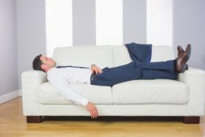 ソファの上に横たわって疲れているビジネスマン