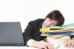 机の上で眠るビジネスマン