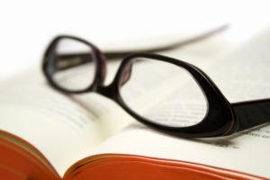 本の上に置かれた黒ぶちの眼鏡