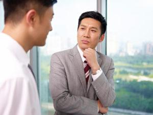 険しい顔で会話を聞く男性