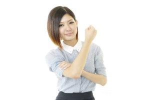 袖を上げてガッツポーズをする女性