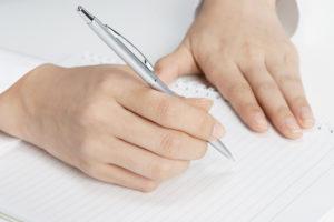 文字を書いている男性