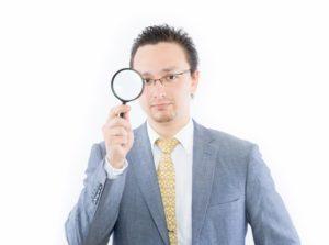虫眼鏡を持つビジネスマン